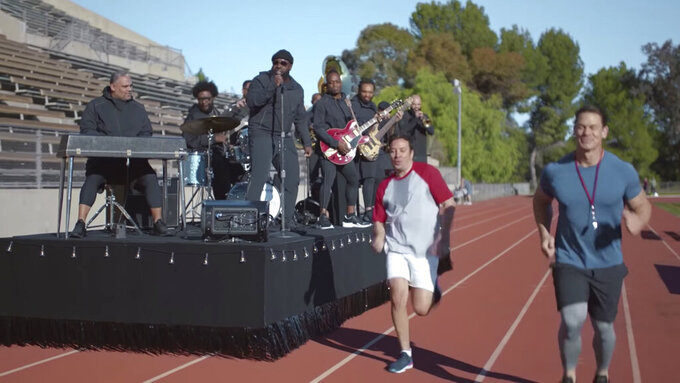 This undated image provided by Michelob ULTRA shows John Cena, right, Jimmy Fallon, center, and the Roots in a scene from the company's 2020 Super Bowl NFL football spot.  Michelob Ultra stresses its low calories and low carbs in an ad that shows talk show host Jimmy Fallon and wrestler John Cena working out. (Michelob ULTRA via AP)