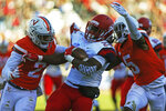 Liberty's running back Frankie Hickson (23) is tackled by two Virginia defenders in the first half of an NCAA college football game Saturday, Nov. 10, 2018, in Charlottesville, Va. (Zack Wajsgras /The Daily Progress via AP)