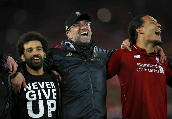 Liverpool's Mohamed Salah, left, manager Jurgen Klopp, center, and Virgil van Dijk celebrate after the Champions League Semi Final, second leg soccer match between Liverpool and Barcelona at Anfield, Liverpool, England, Tuesday, May 7, 2019. Liverpool won the match 4-0 to overturn a three-goal deficit to win the match 4-3 on aggregate. (Peter Byrne/PA via AP)