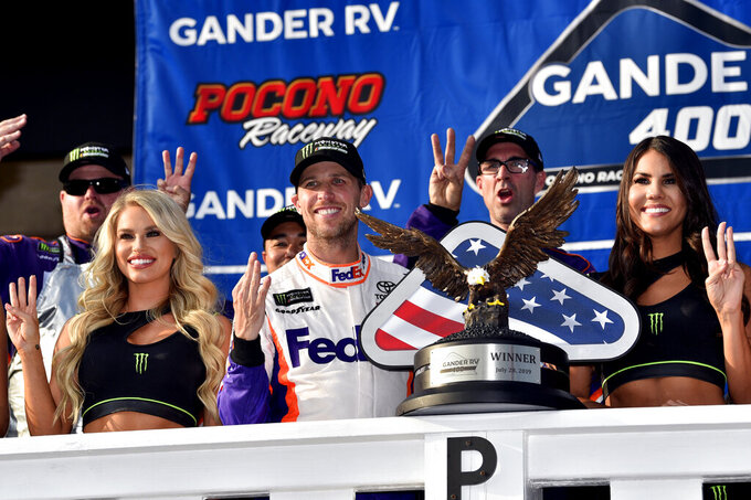 Denny Hamlin, front center, celebrates in Victory Lane after winning a NASCAR Cup Series auto race, Sunday, July 28, 2019, in Long Pond, Pa. (AP Photo/Derik Hamilton)