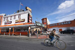 A cyclist passes by a less busy Geno's Steaks in Philadelphia on Tuesday, March 24, 2020. Non-essential businesses are closed and a stay-at-home order has been issued by the city, with exceptions to allow people to purchase essential goods and food or seek medical attention, to try to reduce the spread of the coronavirus. Outdoor activities such as walking, running and cycling are permitted under the order. (Jessica Griffin/The Philadelphia Inquirer via AP)