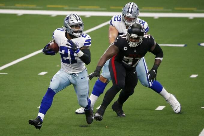 Dallas Cowboys running back Ezekiel Elliott (21) runs the ball as offensive guard Connor Williams (52) helps against pressure from Atlanta Falcons defensive tackle Grady Jarrett (97) in the first half of an NFL football game in Arlington, Texas, Sunday, Sept. 20, 2020. (AP Photo/Michael Ainsworth)