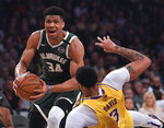 FILE - In this March 6, 2020, file photo, Milwaukee Bucks forward Giannis Antetokounmpo (34) knocks down Los Angeles Lakers forward Anthony Davis as he drives to the basket during the first half of an NBA basketball game in Los Angeles. Antetokounmpo is spending much of his time during the coronavirus-imposed hiatus working out, helping care for his newborn son and playing occasional video games. What the reigning MVP isn't doing very often is shooting baskets now that the NBA has closed down team practice facilities. (AP Photo/Mark J. Terrill, File)