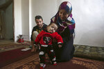 In this February 22, 2018 photo, Syrian refugees Alaa Zatima and his wife Sara al-Matoura, pose with their daughter, one-year-old Eman, in their home in Jerash, Jordan. On Monday, March 5, 2018, Eman, who has a heart defect, received a life-saving pro bono surgery from doctors sent by the Vatican's Bambino Gesu Hospital. The infant is one of the few lucky Syrian refugees with severe medical conditions to get the needed treatment. Dozens more are left untreated each month because of funding constraints in overwhelmed refugee host countries in the region. (AP Photo/Raad Adayleh)