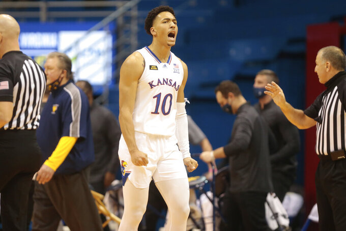 Kansas forward Jalen Wilson yells as the Jayhawks increase their lead against West Virginia during the second half of an NCAA college basketball game Tuesday, Dec. 22, 2020, in Lawrence, Kan. (Evert Nelson/The Topeka Capital-Journal via AP)