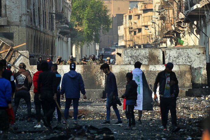 Anti-government protesters gather near barriers set up by security forces to close Rasheed Street during ongoing protests in Baghdad, Iraq, Thursday, Dec. 5, 2019. (AP Photo/Khalid Mohammed)