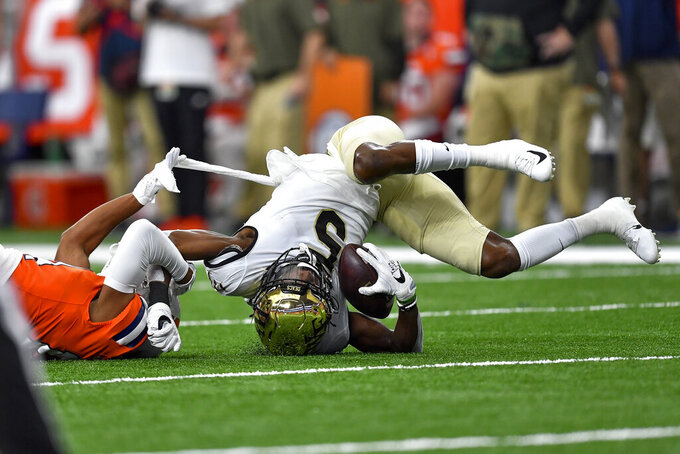 Wake Forest wide receiver Jaquarii Roberson (5) is tackled by Syracuse defensive back Jason Simmons (14) during the first half of an NCAA college football game in Syracuse, N.Y., Saturday, Oct. 9, 2021. (AP Photo/Adrian Kraus)