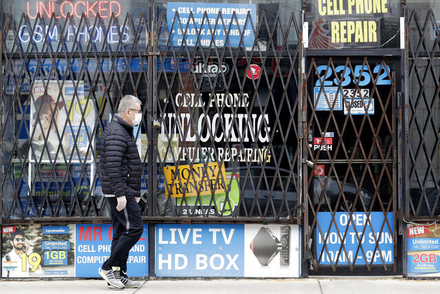 FILE - In a  April 30, 2020 file photo, a man walks by a closed store during the COVID-19 in Chicago. Layoffs are declining and hiring is slowly picking up, yet it's not really clear where the job market goes next.  (AP Photo/Nam Y. Huh, File)