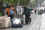 Protesters move items in place to block the street after Seattle Department of Transportation workers removed concrete barricades at the intersection of 10th Ave. and Pine St., Tuesday, June 30, 2020 at the CHOP (Capitol Hill Occupied Protest) zone in Seattle. The area has been occupied by protesters since Seattle Police pulled back from their East Precinct building following violent clashes with demonstrators earlier in the month. (AP Photo/Ted S. Warren)