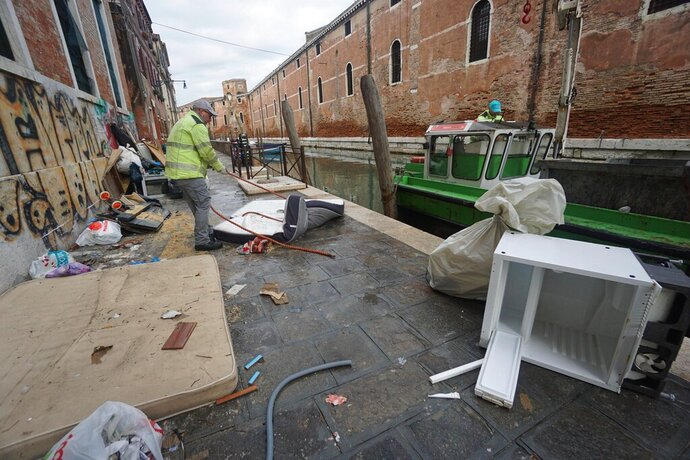People remove damaged items from an alley in Venice, northern Italy, Monday, Nov. 18, 2019. Venetians have been coping with almost a week of exceptional tides that flooded most of the city and caused damage that has been estimated at hundreds of millions of euros (dollars).  (Andrea Merola/ANSA via AP)