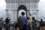 """People stroll around the wrapped Arc de Triomphe monument Saturday, Sept. 18, 2021, in Paris. The """"Arc de Triomphe, Wrapped"""" project by late artist Christo and Jeanne-Claude is on view until Oct. 3. Visitors to the famous Napoleonic arch, which dominates the Champs-Elysees Avenue, will not only be able to see the gleaming silver and blue fabric, but to touch it too — as the artists had intended. (AP Photo/Lewis Joly)"""