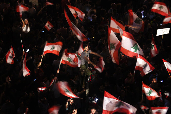 FILE - In this Oct. 21, 2019 file photo, anti-government protesters wave Lebanese flags and chant,