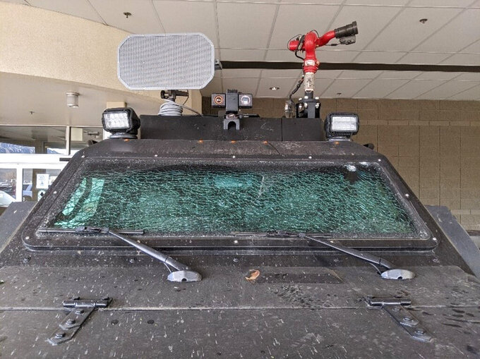 This Sunday, March 7, 2021, photo released by the City of Boulder shows the smashed windshield of a Terradyne light armored patrol vehicle at the Boulder Police Department in Boulder, Colo. Boulder Police confirms three members of their SWAT team were injured with bricks and rocks. They also say their armored rescue vehicle and fire truck sustained heavy damage. Authorities say they will seek criminal charges against participants in a massive party near the University of Colorado that devolved into a violent confrontation with police this weekend. (Boulder Police Department/ City of Boulder via AP)