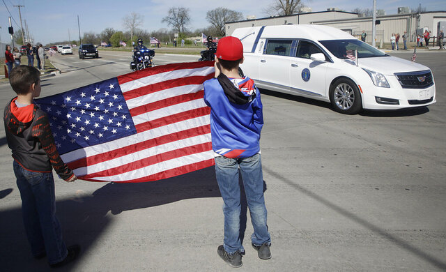Brothers Colton and Ryder Stephens hold an American flag as they watch the procession for the body of Air Force Staff Sgt. Marshal D. Roberts Wednesday, March 25, 2020, in Tulsa, Okla.Roberts, 28, of Owasso, was killed on March 11 while deployed in support of Operation Inherent Resolve in Iraq. Roberts was a member of the 219th Engineering Installation Squadron, 138th Fighter Wing, headquartered in Tulsa. (Mike Simons/Tulsa World via AP)