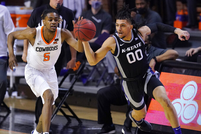 Kansas State guard Mike McGuirl (00) brings the ball up the court in front of Oklahoma State guard Rondel Walker (5) in the first half of an NCAA college basketball game Saturday, Feb. 13, 2021, in Stillwater, Okla. (AP Photo/Sue Ogrocki)