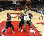 Boston Celtics center Al Horford (42) goes up for a shot as Chicago Bulls center Robin Lopez, left, forward Otto Porter Jr. (22) and forward Lauri Markkanen (24) defend him during the first half of an NBA basketball game Saturday, Feb. 23, 2019, in Chicago. (AP Photo/David Banks)