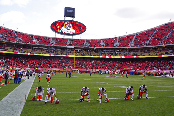 Cleveland Browns players kneel on the field before an NFL divisional round football game against the Kansas City Chiefs, Sunday, Jan. 17, 2021, in Kansas City. (AP Photo/Charlie Riedel)