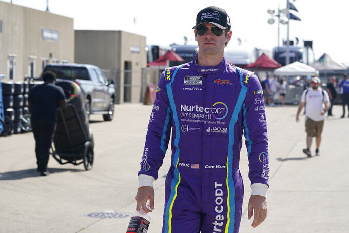 Cody Ware walks to his garage before practice for the NASCAR Cup Series at Indianapolis Motor Speedway, Saturday, Aug. 14, 2021, in Indianapolis. (AP Photo/Darron Cummings)