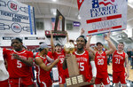 Boston University's Jonas Harper (15) holds the trophy after beating Colgate  in the NCAA Patriot League Conference basketball  championship at Cotterell Court, Wednesday, March 11, 2020, in Hamilton, N.Y. (AP Photo/John Munson)