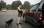 Diane Nuccio pauses while packing her car beside her dog Railey at a shelter for people fleeing the Carr Fire, Friday, Aug. 10, 2018, in Redding, Calif. The only items Nuccio has left fit in her car after her home burned in the fire. (AP Photo/John Locher)