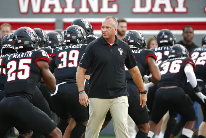 North Carolina State head coach Dave Doeren works with his team prior to an NCAA college football game against Ball State in Raleigh, N.C., Saturday, Sept. 21, 2019. (AP Photo/Karl B DeBlaker)