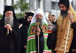 Head of the Serbian Orthodox Church, Patriarch Porfirije, center, and Mitropolitan Joanikije, left, at the arrival ceremony in front of the Serbian Orthodox Church of Christ's Resurrection in Podgorica, Montenegro, Saturday, Sept. 4, 2021. Serbian patriarch Porfirije arrives at Podgorica ahead of the inauguration of the new bishop of the Serbian Orthodox Church in Montenegro scheduled in the historic capital of Cetinje, sparking tensions. On Saturday, hundreds of protesters confronted the police in Cetinje and briefly removed some of the protective metal fences around the monastery where the inauguration of Mitropolitan Joanikije is supposed to take place. (AP Photo/Risto Bozovic)
