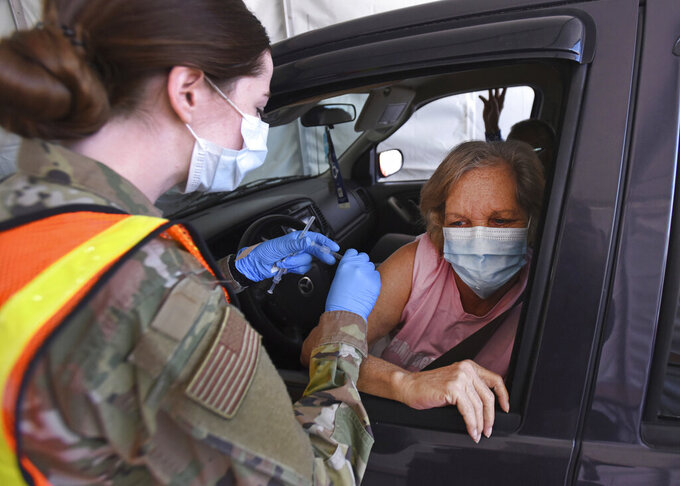 Susan Morehead of Greensboro receives her COVID-19 vaccination from Air Force medical technician Jade Loftus at the FEMA-supported mass vaccination site outside Four Season Town Centre mall, Wednesday, March 10, 2021, in Greensboro, N.C. Wednesday was the first full day of vaccinations at the site which includes both indoor and drive-thru vaccinations. (Walt Unks/The Winston-Salem Journal via AP)