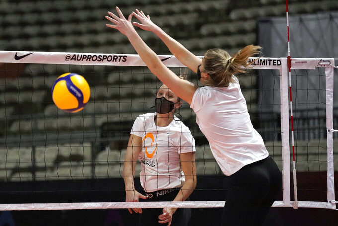 FILE - In this Feb. 24, 2021, file photo, Jordan Larson hits past defender Karsta Lowe, right, during a volleyball workout at Fair Park Coliseum, in Dallas. Larson was a player and coach while winning the inaugural championship of a unique women's professional indoor volleyball league focused on individual stats over team results. (AP Photo/Tony Gutierrez, File)