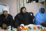 Asina Selemani, center, the widow of World Food Programme (WFP) driver Moustapha Milambo, who was killed in the attack on a U.N. convoy that also killed the Italian ambassador to Congo and an Italian Carabinieri police officer, sits at her home in Goma, North Kivu province, Congo, Tuesday, Feb. 23, 2021.  An Italian Carabinieri unit is expected in Congo Tuesday to investigate the killings of the Italian ambassador to Congo, an Italian Carabinieri police officer and their driver in the country's east. (AP Photo/Justin Kabumba)