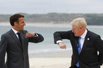 British Prime Minister Boris Johnson, right, greets French President Emmanuel Macron during arrivals for the G7 meeting at the Carbis Bay Hotel in Carbis Bay, St. Ives, Cornwall, England, Friday, June 11, 2021. Leaders of the G7 begin their first of three days of meetings on Friday, in which they will discuss COVID-19, climate, foreign policy and the economy. (Phil Noble, Pool via AP)