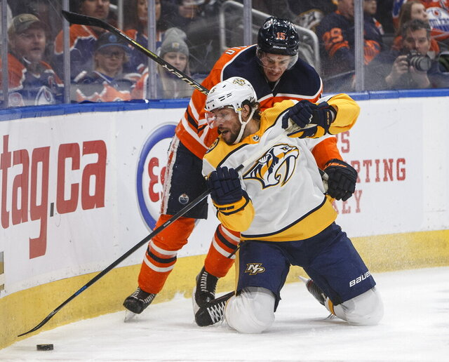 Nashville Predators' Craig Smith (15) and Edmonton Oilers' Josh Archibald (15) battle for the puck during first period NHL hockey action in Edmonton, Alberta, Tuesday, Jan. 14, 2019. (Jason Franson/The Canadian Press via AP)