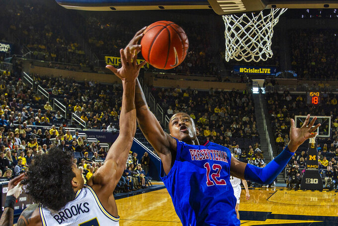 Presbyterian forward Cory Hightower (12) wins a rebound from Michigan guard Eli Brooks (55) in the first half of an NCAA college basketball game at Crisler Center in Ann Arbor, Mich., Saturday, Dec. 21, 2019. (AP Photo/Tony Ding)