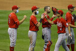 Cincinnati Reds' Joey Votto, left, and Jesse Winker, second from left, celebrate with teammates after the first baseball game of a doubleheader against the Milwaukee Brewers, Thursday, Aug. 27, 2020, in Milwaukee. (AP Photo/Aaron Gash)