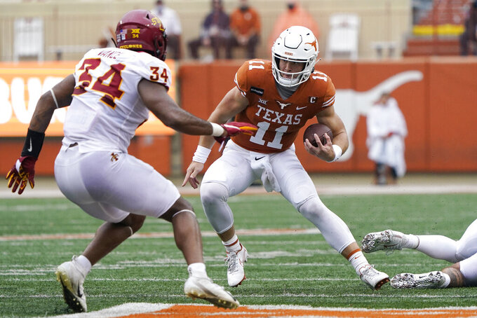 Texas quarterback Sam Ehlinger (11) runs against Iowa State linebacker O'Rien Vance (34) during the first half of an NCAA college football game, Friday, Nov. 27, 2020, in Austin, Texas. (AP Photo/Eric Gay)
