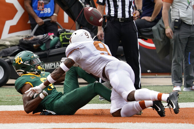 Baylor's Tyquan Thornton, left, misses a catch as Texas' Josh Thompson, right, defends during the first half of an NCAA college football game in Austin, Texas, Saturday, Oct. 24, 2020. (AP Photo/Chuck Burton)