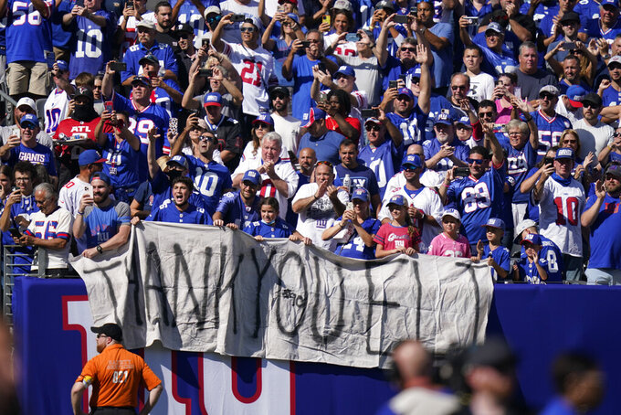 Fans honor former New York Giants quarterback Eli Manning as he addresses the crowd during a ceremony to retire his jersey number 10 and celebrate his tenure with the team during half-time in an NFL football game against the Atlanta Falcons, Sunday, Sept. 26, 2021, in East Rutherford, N.J. (AP Photo/Seth Wenig)