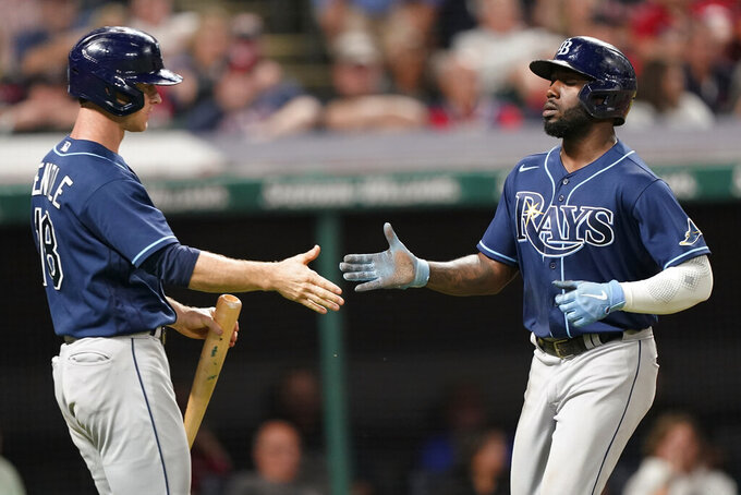 Tampa Bay Rays' Randy Arozarena, right, is congratulated by Joey Wendle after Arozarena scored in the 10th inning of the team's baseball game against the Cleveland Indians, Thursday, July 22, 2021, in Cleveland. Tampa won 5-4 in 10 innings. (AP Photo/Tony Dejak)