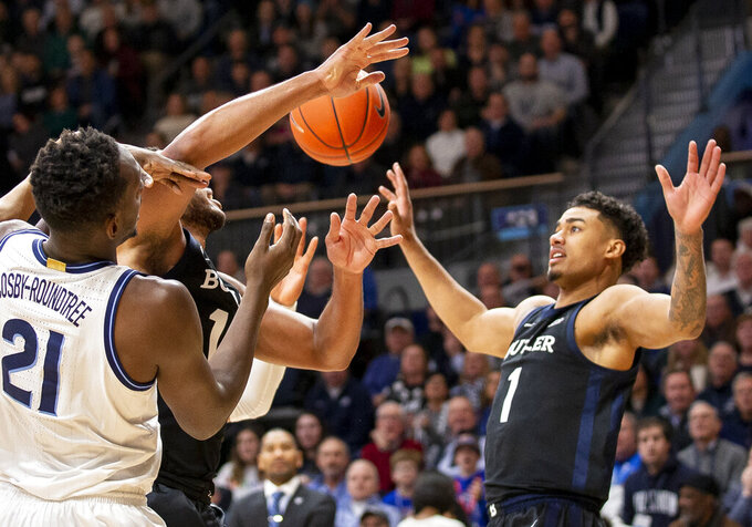 Villanova forward Dhamir Cosby-Roundtree (21) and Butler forward's Bryce Nze (10) and Jordan Tucker (1) reach for a rebound during the first half of an NCAA college basketball game, Tuesday, Jan. 21, 2020, in Villanova, Pa. (AP Photo/Laurence Kesterson)