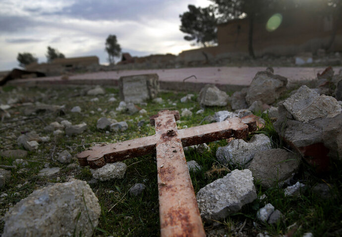 FILE - This April 1, 2018 file photo, shows a cross that lies in the rubble of a destroyed church that was blown up by Islamic State militants in 2015, in the deserted village of Tal Jazeera, northern Syria. The Qatar-based Syrian Network for Human Rights, a Syrian war monitor associated with the opposition said in its report Monday, Sept. 9, 2019, that over 120 Christian places of worship have been damaged or destroyed by all sides in the country's eight-year conflict. (AP Photo/Hussein Malla, File)