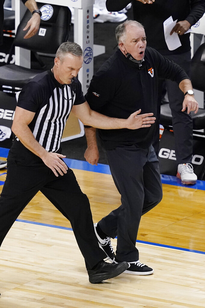 A ref keeps Virginia Tech head coach Mike Young off the court during the first half of an NCAA college basketball game against North Carolina in the quarterfinal round of the Atlantic Coast Conference tournament in Greensboro, N.C., Thursday, March 11, 2021. (AP Photo/Gerry Broome)