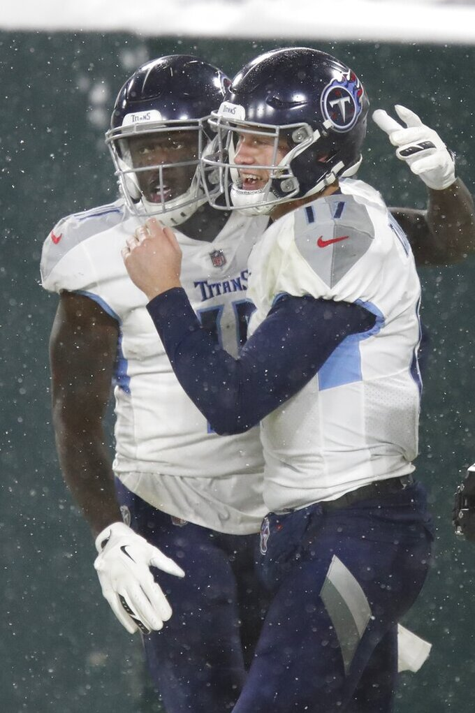 Tennessee Titans' Ryan Tannehill celebrates his touchdown run with A.J. Brown during the second half of an NFL football game against the Green Bay Packers Sunday, Dec. 27, 2020, in Green Bay, Wis. (AP Photo/Matt Ludtke)