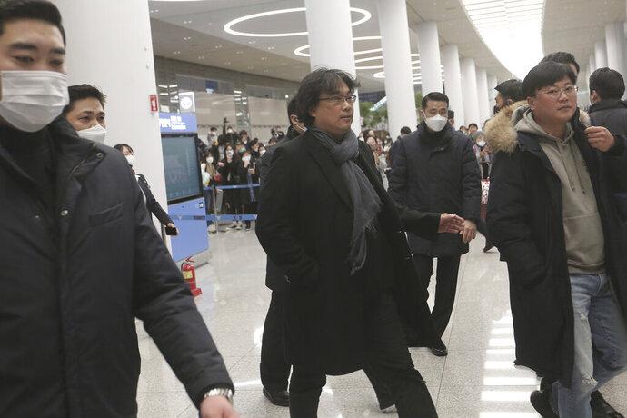 South Korean director Bong Joon-ho, center, arrives at the Incheon International Airport in Incheon, South Korea, Sunday, Feb. 16, 2020. South Koreans are reveling in writer-director Bong's dark comic thriller,
