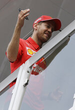 Ferrari driver Sebastian Vettel of Germany gestures on the Ferrari's motorhome at the Monaco racetrack, in Monaco, Wednesday, May 22, 2019. The Formula one race will be held on Sunday. (AP Photo/Luca Bruno)