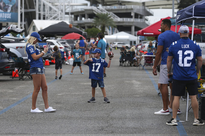 Fans tailgate before an NFL football game between the Jacksonville Jaguars and the Indianapolis Colts, Sunday, Sept. 13, 2020, in Jacksonville, Fla. (AP Photo/Stephen B. Morton)