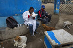 Brother Ronald Marin, a 30-year-old layworker from Venezuela, enjoys a free lunch between burials, at the entrance of the