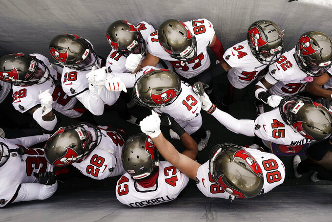 Tampa Bay Buccaneers huddle in a walkway to the field before the NFC championship NFL football game between the Tampa Bay Buccaneers and Green Bay Packers in Green Bay, Wis., Sunday, Jan. 24, 2021. (AP Photo/Morry Gash)