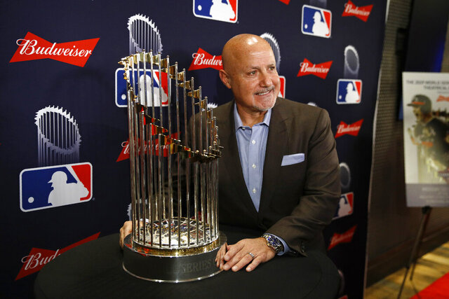 Washington Nationals general manager Mike Rizzo poses with the World Series trophy as he arrives for the premiere of a documentary film on the team's first World Series baseball championship, Monday, Dec. 2, 2019, in Washington. (AP Photo/Patrick Semansky)