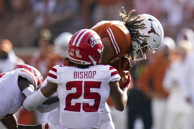Texas wide receiver Jordan Whittington (4) is hit by Louisiana-Lafayette safety Brandon Bishop (25) after a catch during the second half of an NCAA college football game Saturday, Sept. 4, 2021, in Austin, Texas. (AP Photo/Eric Gay)