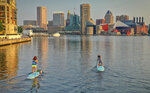 Paddleboarders with stand-up paddleboard company B'More SUP head back toward the marina during a tour of Baltimore's Inner Harbor, Wednesday morning, July 21, 2021. (Jerry Jackson/The Baltimore Sun via AP)