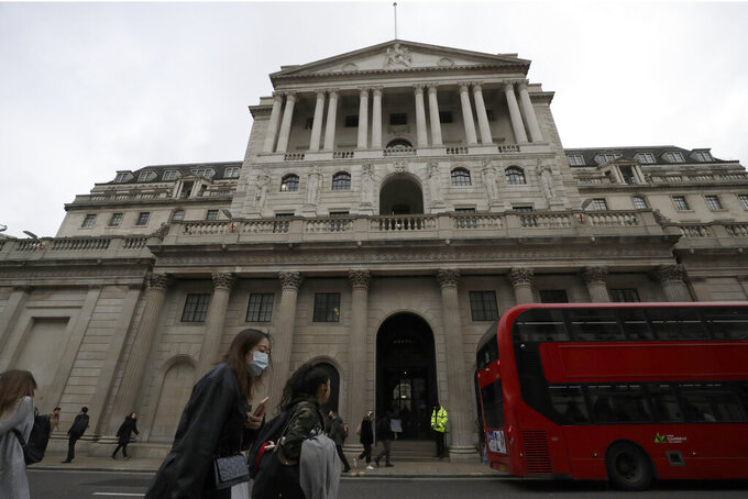 FILE - In this Wednesday, March 11, 2020 file photo, pedestrians wearing face masks walk past the Bank of England in London. The U.K. posted the biggest jump in annual inflation on record last month as global supply shortages and rising wages magnified the scale of price increases after pandemic-related discounts a year ago. (AP Photo/Matt Dunham, File)